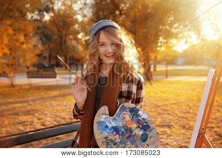 Young female artist with palette and brush in autumn park