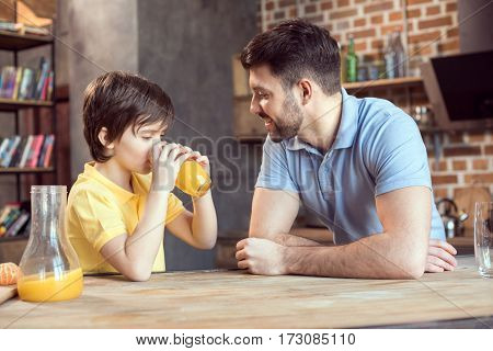 Smiling father looking at cute little son drinking fresh orange juice