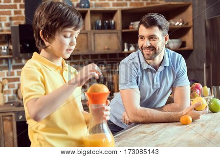 Smiling father looking at little son squeezing fresh juice in kitchen