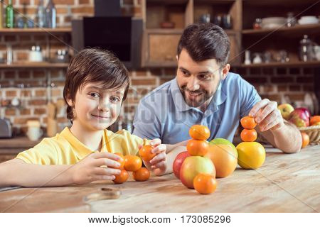 Happy father and son playing with citrus fruits at kitchen table