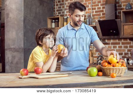 Father and son selecting fruits from basket at kitchen table