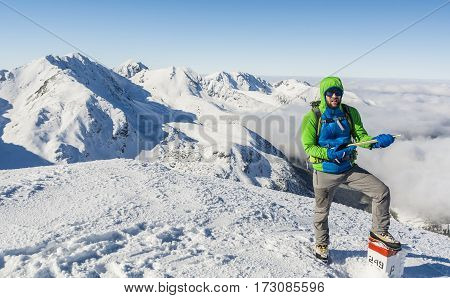 Mountaineer With Ice Axe And Green Blue Jacket.