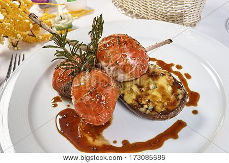 Image of lamb chops on a bed of vegetables Eggplant stuffed with vegetables decorated table romantic dinner