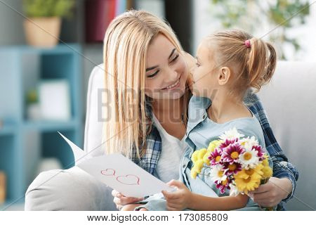 Beautiful young woman and her daughter sitting on sofa with greeting card and bouquet of flowers. Mother's day concept