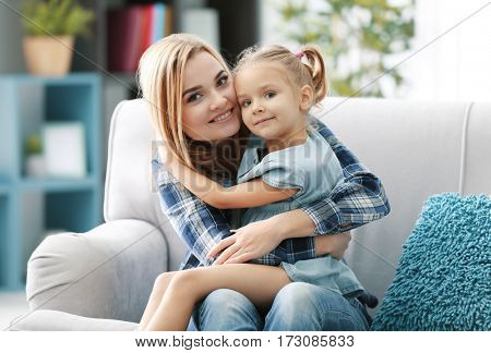Beautiful young woman and her daughter sitting on sofa at home. Mother's day concept