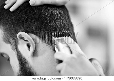 Professional hairdresser making stylish haircut for man, toned in black and white