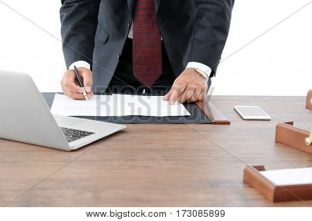 Successful businessman signing documents in office, close up view