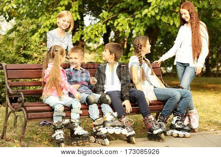 Cheerful children with roller skates sitting on bench in park