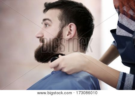 Professional hairdresser cleaning handsome client face with brush