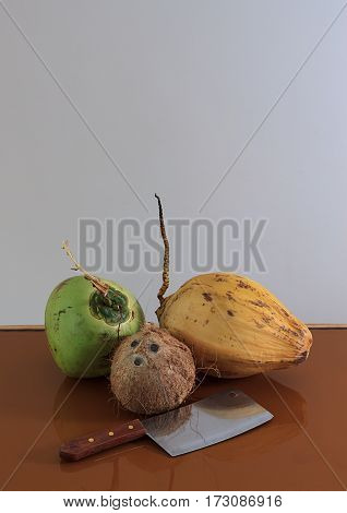 three different coconuts with machete on table with copy space