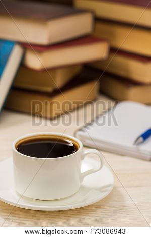 Notebook with pen on a wooden table in front of the window. A cup of hot coffee on the table.