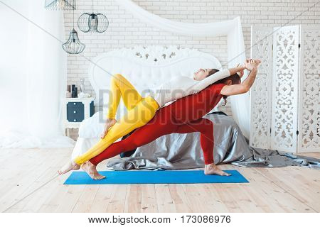 Couple yoga sessions after sleeping at home in the bedroom.