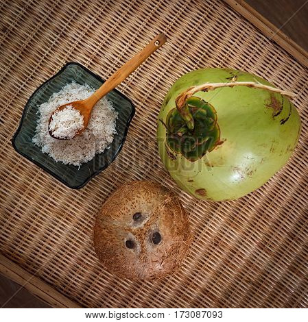 young and old coconuts with bowl full of coconut flakes on table top view