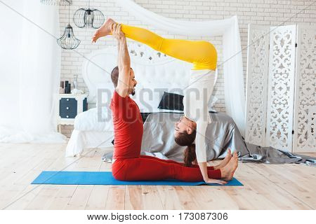 Young people practice yoga in the morning in her bedroom.