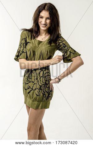 Young slim brunette girl dancing in a short dress