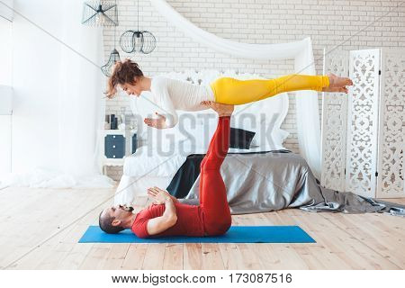 Couple yoga sessions at home in the bedroom.