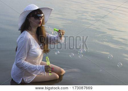 white woman in sun hat make blow bubbles on beach lake