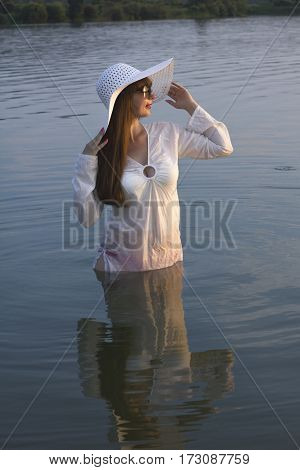 white woman in sun hat posture on lake