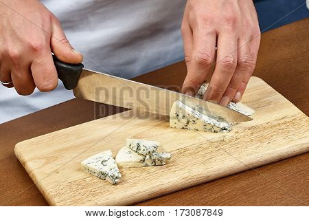 cutting cheese on a wooden cooking board male hands chef