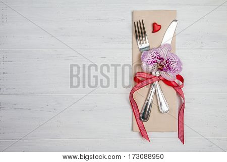 Silverware On Beige Napkins With Orchid Flower