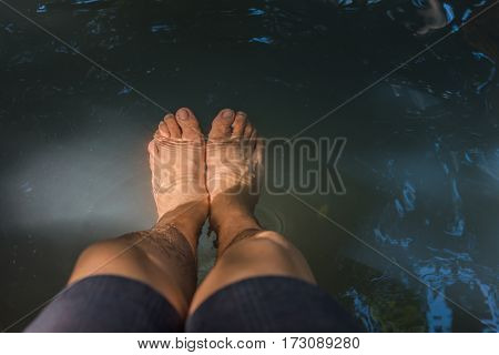 image of barefoot soak in hot spring stream day time for relaxation.