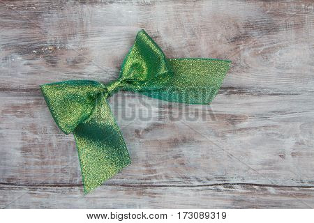 Green Shiny Bow On Light Wooden Background