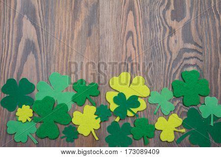Green Leaves Of Clover Shamrock, Quatrefoil On Wooden Table