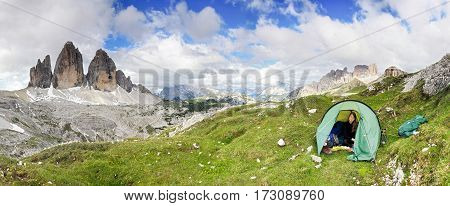 Female mountaineer sitting relaxed in tent and smiling happy after a night outside in the mountains. Great mountain view to the Tre Cime, Three Peaks in background. Alps, Dolomites, Italy.