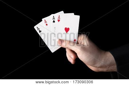 human hand holding four aces on a black background