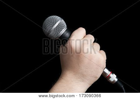 man's hand holding a microphone on a black background