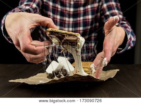 Womans Hands Pick Up Gooey Marshmallow Smore with sticky fluff