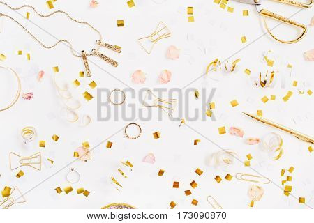 Beauty blog background. Gold style feminine accessories pattern. Golden tinsel scissors pen rings necklace bracelet on white background. Flat lay top view.