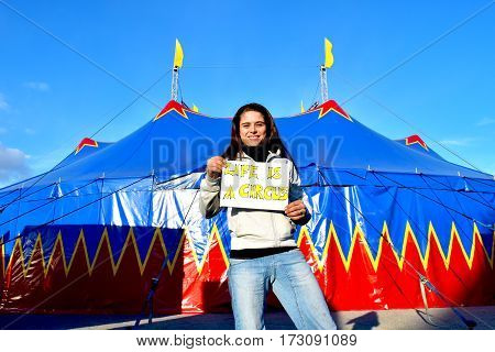 Girl is holding a sign, live is a circus, in front of a circus tent, blue and red