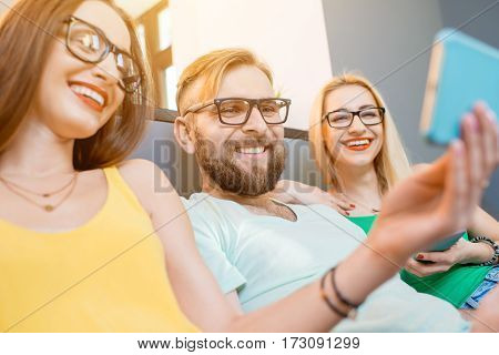 Young friends sitting with smart phones on the couch at home