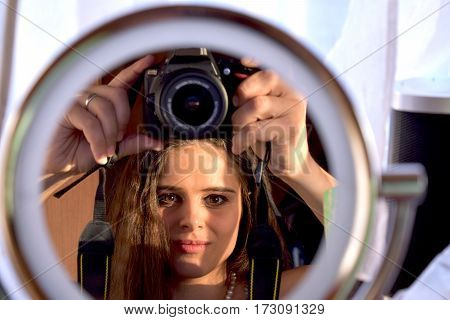 girl is taking a selfie in a mirror with a reflex camera SLR