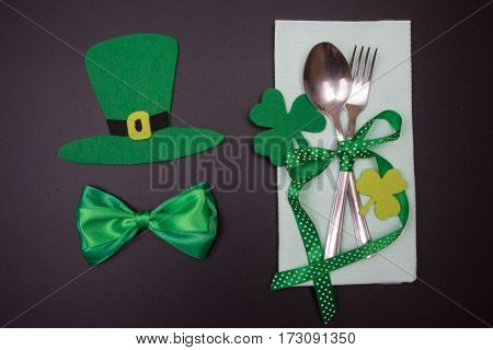 Tableware On Blackboard In St. Patricks Day. Cutlery With Green Ribbon