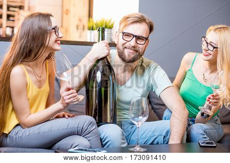 Young friends drinking wine with big bottle sitting on the couch at home