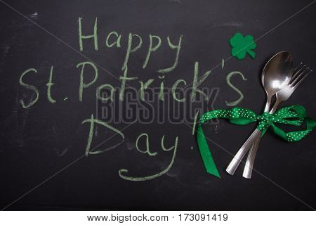 Spoon And Fork On Blackboard With Words Happy St. Patricks Day