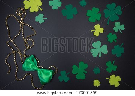 Satin Bow, Shamrocks And Quatrefoil On Blackboard. St. Patricks Day