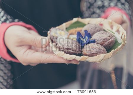 female Asian hand hold Thai style Sweet and Savory Grilled Coconut Rice Hotcakes dessert in banana leaf plate.