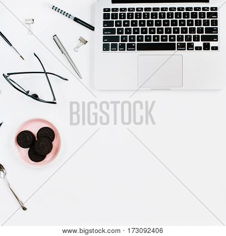 Pale pink stylish home office workspace desk with laptop cookies glasses and office stuff on white background. Flat lay top view. Entrepreneur office concept.