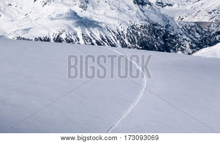 Ski track on untracked snow field after recent snowfall on Glacier du tour dividing into two paths leading different ways down the in the Alps in winter