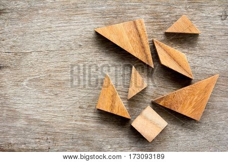 Tangram puzzle wait for complete on wooden table background