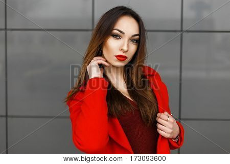 Young Woman In Red Clothes Is Posing Near The Gray Wall