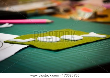 Manual cutting letters with colored sheets of felt