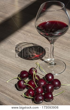 One wineglass with red wine and cherries on the brown wooden background with shadows