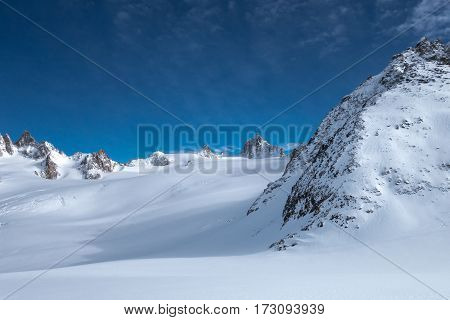 Snow covered Glacier du Tour vistas with peaks and crags in foreground and background under blue and sunny sky in the Alps in winter