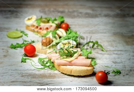 Sandwich with ham and sandwich with hot dog-frankfurter on rustic table
