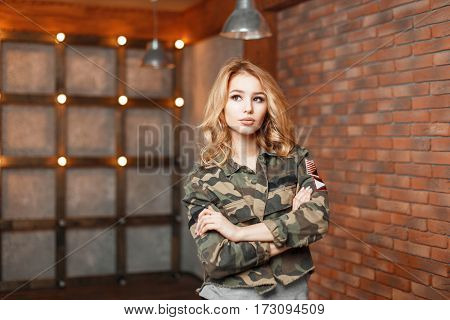 Stylish Young Woman In Trendy Military Jacket Standing Near The Wall With Lights