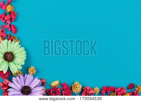 Dried flowers, exotic leaves and plants border frame on blue background. Top view, flat lay. Copy space for text